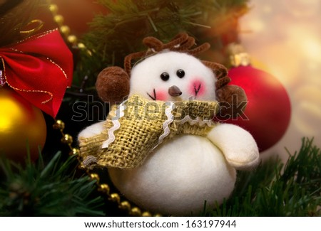 Funny snowman in scarf decoration on christmas tree background