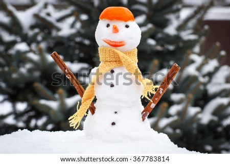 Funny snowman wrapped woolen scarf with tangerine peel on head, snow covered coniferous tree background, concept of winter season - stock photo