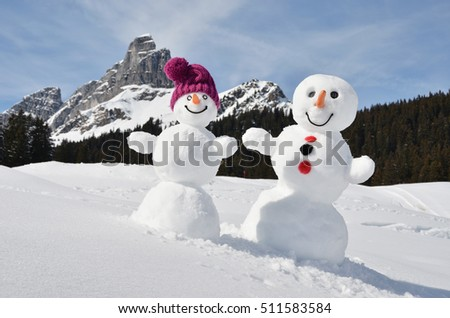 Funny snowmen against Swiss Alps