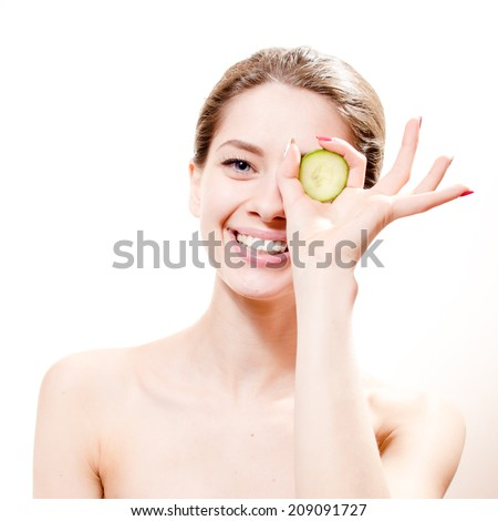 funny spa: young beautiful woman standing with slice of cucumber in the hand one piece on eye isolated on white background, portrait