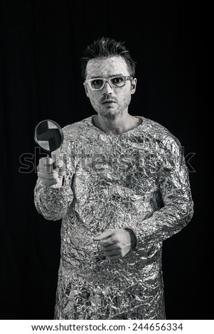 Funny spaceman holding magnifying glass. - stock photo