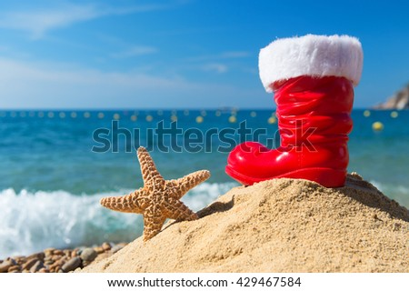 Funny starfish and red boot from Santa Claus at the beach for Christmas - stock photo