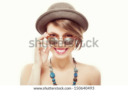 Funny summer portrait of beautiful smiling girl in sunglasses and hat, looking at camera