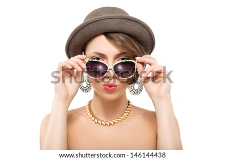 Funny summer portrait of girl in hat with funny face, holding sunglasses with hands