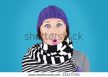 Funny surprised face woman with wool hat and stripe black and white scarf: humorous winter concept