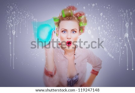 Funny surprised housewife with rag / wipe cleaning window / glass . Foam / soap on glass - stock photo