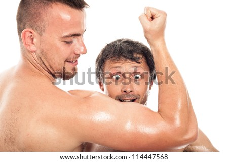 Funny surprised man looking at young muscular sports man biceps, isolated on white background. - stock photo