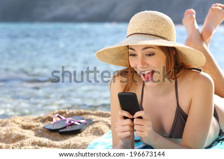 Funny surprised woman watching social media in a smart phone on the beach on vacations                 - stock photo