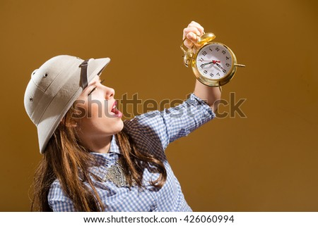 Funny surprised young woman in checkered shirt and pith helmet holding alarm clock over brown background - stock photo