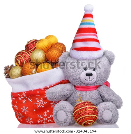 Funny teddy bear in hat with santa claus bag full of toys isolated over white background - stock photo