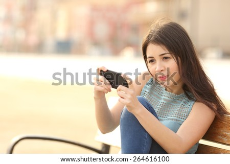 Funny teenager girl playing games on a smart phone sitting in a bench in a park - stock photo