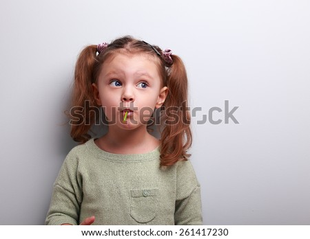 Funny thinking kid girl eating lollipop and looking up on grey background - stock photo
