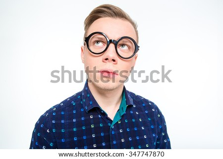 Funny thoughtful male in in plaid shirt and round glasses looking up and thinking over white background