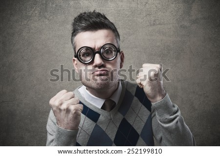 Funny threatening guy with fists raised staring at camera - stock photo