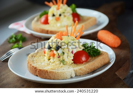 Funny toast for kids breakfast: chicken shaped egg salad on toasted white american bread - stock photo