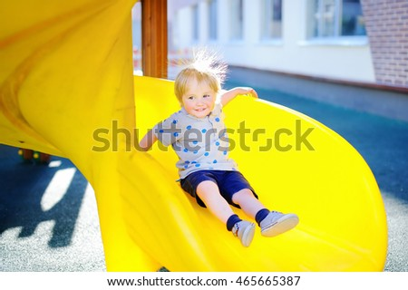 Funny toddler boy having fun on slide on playground