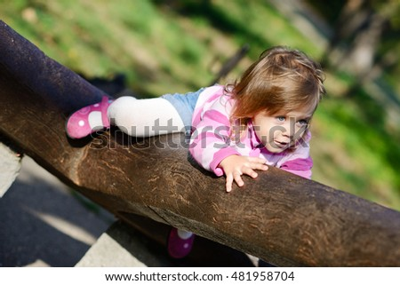 funny  toddler girl climbing on the walk