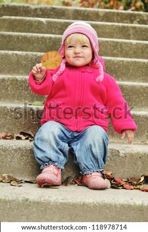 funny toddler girl holding leaf - stock photo