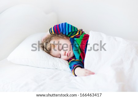 Funny toddler girl sleeping in a white bed