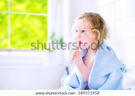 Funny toddler girl with curly hair and big eyes in a blue hooded towel after shower sitting in a white sunny bathroom brushing her teeth next to a window