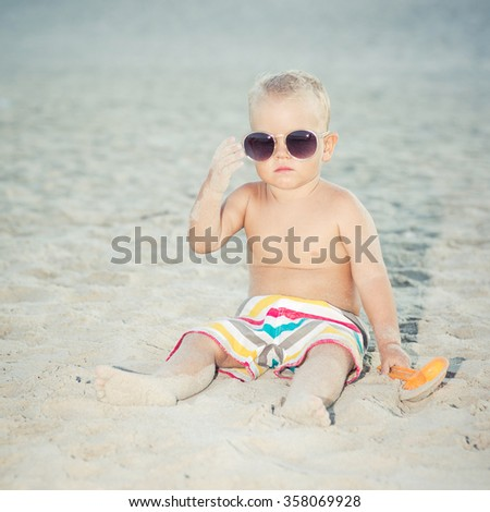 Funny toddler wearing oversized sunglasses