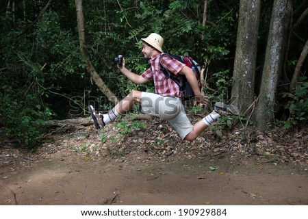 funny tourist with a camera running in the woods - stock photo