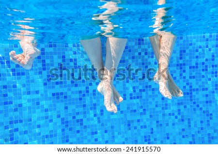 Funny underwater family legs in swimming pool, vacation and sport concept  - stock photo