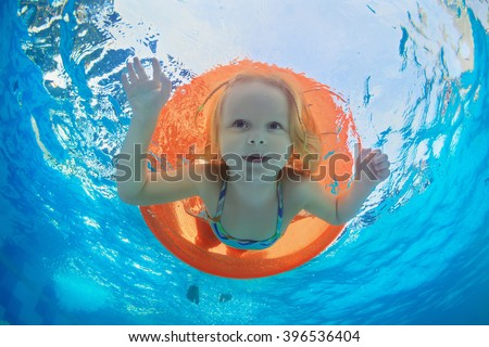 Funny underwater photo of baby girl swimming with fun on orange tube and diving in clear aqua park pool. Healthy family lifestyle, and children water sports activity,  with parents on summer vacation. - stock photo