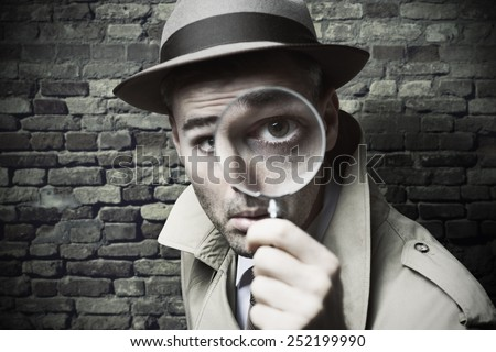 Funny vintage detective looking through a magnifier - stock photo