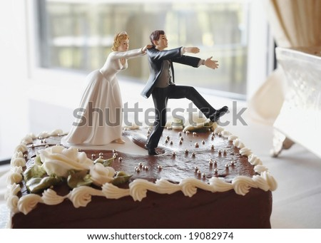 Funny wedding cake top, bride chasing groom - stock photo