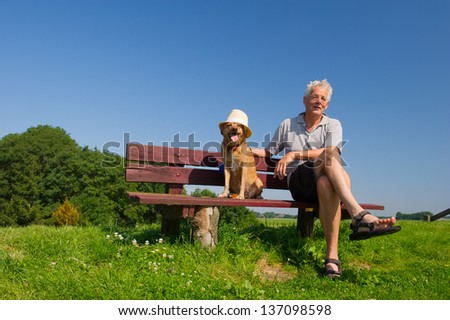 Funny wet dog with hat on bench outdoor with his owner sitting in nature landscape - stock photo