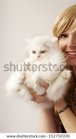 Funny white Persian kitten held by a pretty girl - stock photo