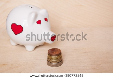Funny white with red hearts piggy bank staying near euro coins on wooden background. - stock photo