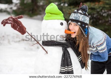 Funny winter woman making snowman. daylight - stock photo