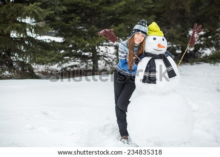 Funny winter young woman with snowman. focus on woman - stock photo