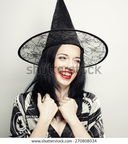 Funny Witch. Young happy woman with canival hat. Studio shot. - stock photo