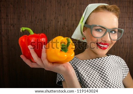 Funny woman cook holading sweet pepper, close up-FOCUS ON PEPPER - stock photo
