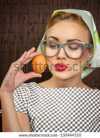 Funny woman cook holding egg,close-up - stock photo