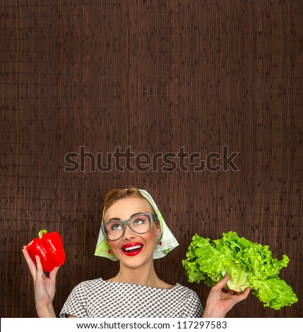 Funny woman cook holding salad and sweet pepper, space for yuor text