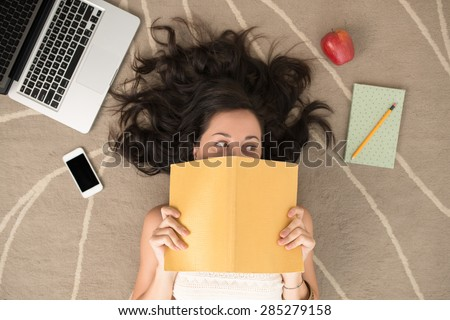 Funny woman covering her face with notebook - stock photo