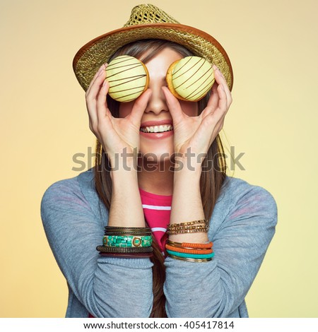 Funny woman hold two cake in front of eyes. Hipster girl.