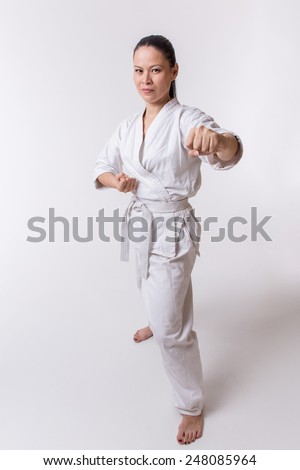 Funny woman in kimono show punch in martial art exercise on white - stock photo