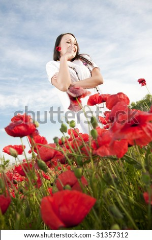 Funny woman in poppy field - stock photo