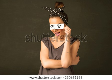 Funny woman looking with hand drawn paper eyes - stock photo