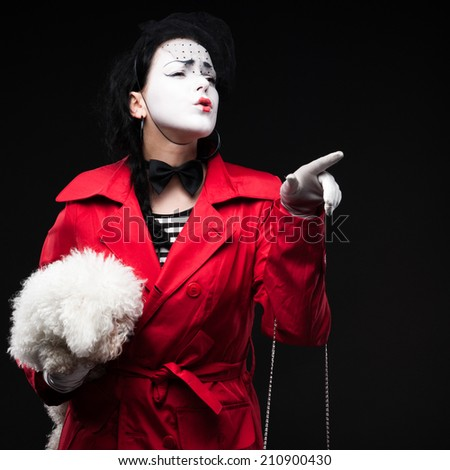 funny woman mime holding small fluffy dog and showing emotions - stock photo