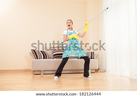 funny woman mopping floor and playing. beautiful girl playing music using mop - stock photo