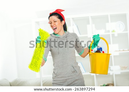 Funny woman mopping floor and singing - stock photo