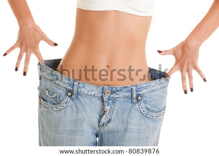 Funny woman shows her weight loss by wearing an old jeans, isolated on white background - stock photo
