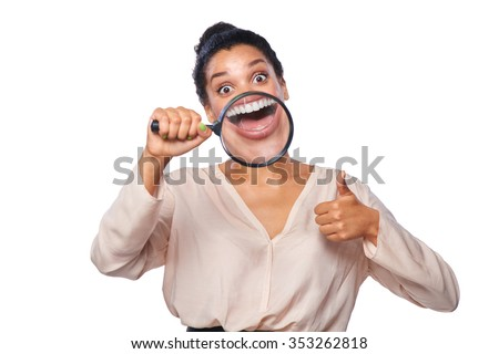 Funny woman smiling and showing teeth through a magnifying glass, gesturing thumb up, over white background - stock photo