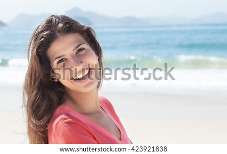 Funny woman with dark hair at beach with ocean and blue sky in the background - stock photo